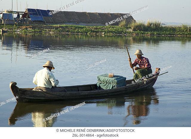 local men fishing in canoe boat Sunrise over the lake near wooden foot bridge U Bein Bridge crossing the Taungthaman Lake near Amarapura in Mandalay Myanmar