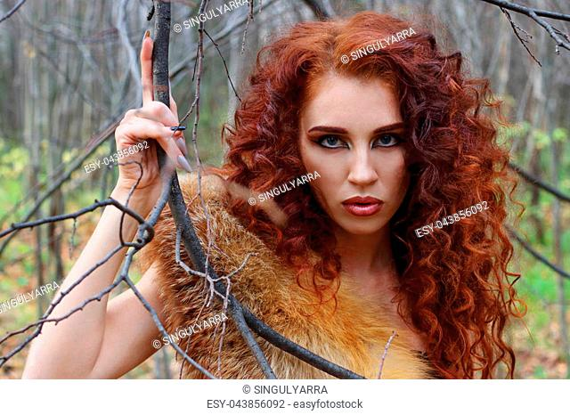 Pretty young woman poses among tree branches in autumn forest