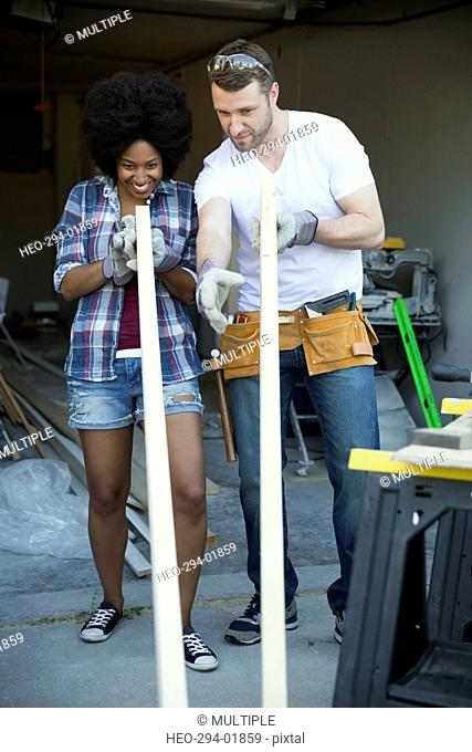 Couple examining wood for home improvement project in garage