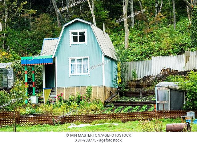 Typical wooden dacha cottage and garden in rural area of Kunashir Isand in the Kuril Island chain in Russian far East