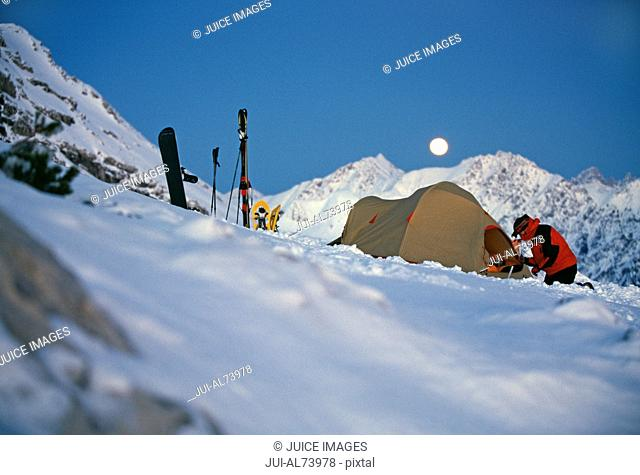 View of a young man setting up camp in the snow, Bivouac, Nebelhorn area, Bavaria, Germany