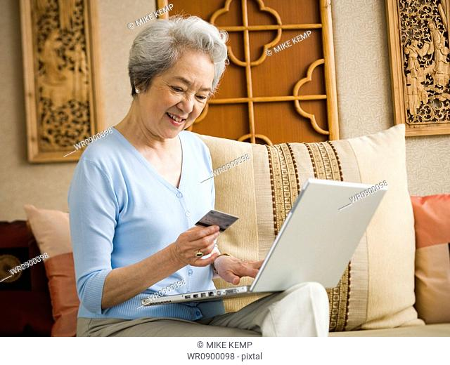 Woman sitting on sofa with laptop and credit card smiling