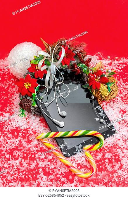 Tablet with headphones and candy best Christmas gift on a red background decorated christmas flower