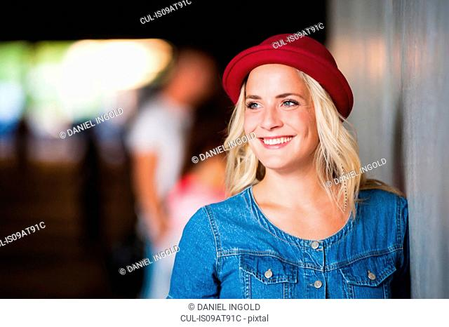 Young woman wearing red hat leaning against wall