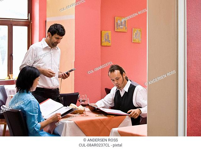 Waiter taking orders from customers
