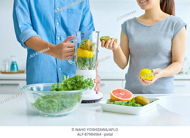 Japanese couple making smoothie in the kitchen