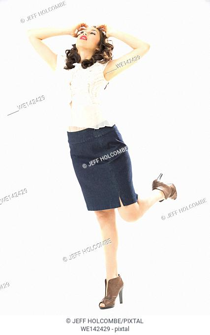 Beautiful young woman in white blouse and blue denim skirt, full length in brown heels, hands on head, looking up while standing on one foot