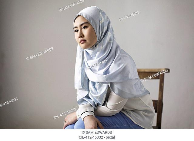 Thoughtful young woman in blue silk hijab