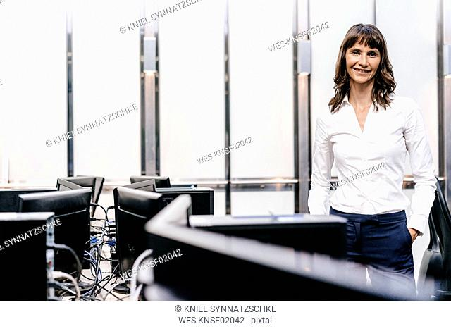 Successful businesswoman standing in office, looking at camera