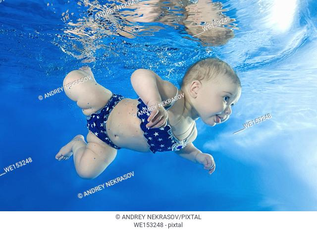 Little girl swims under the water