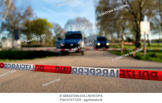 Marked police vehicles and police barrier tape cordon off the accesses road to the Hotel Seefugium near Isernhagen, Germany, 21 April 2016
