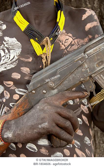 Karo warrior with body paintings and a rifle, Omo river valley, Southern Ethiopia, Africa