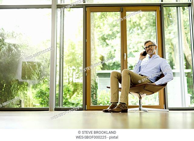 Man on the phone sitting on chair in his living room