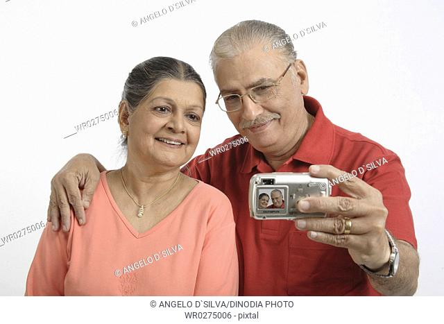 Old couple , man holding digital camera and trying to click their photograph MR 703B and 703A
