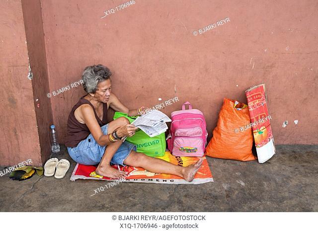 A Filipino woman reading the newspaper on the sidewalk  Cebu City, Cebu, Visayas, Philippines