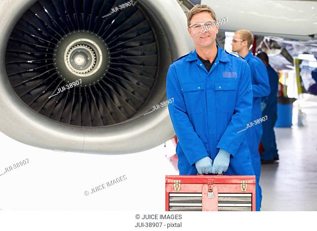 Portrait of confident engineer holding tool box next to engine of passenger jet in hangar