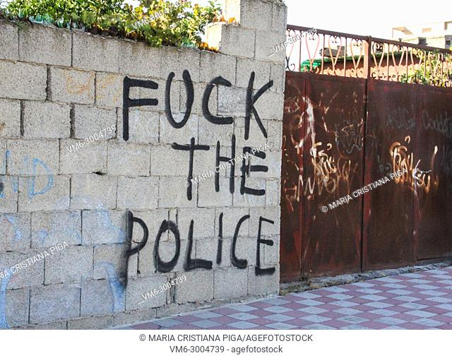 Graffiti in a breeze block wall against the police with rusty gates in Cagliari, Sardinia, Italy