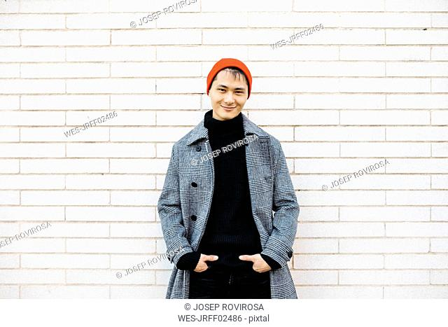 Portrait of stylish young man wearing cap, black turtleneck pullover and grey coat