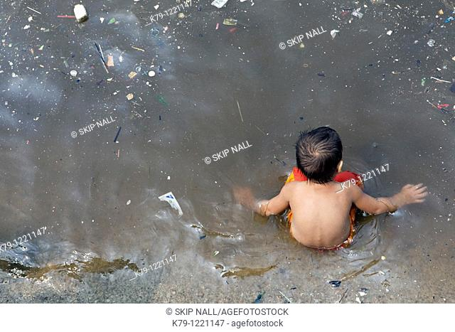 Little boy sitting in polluted water