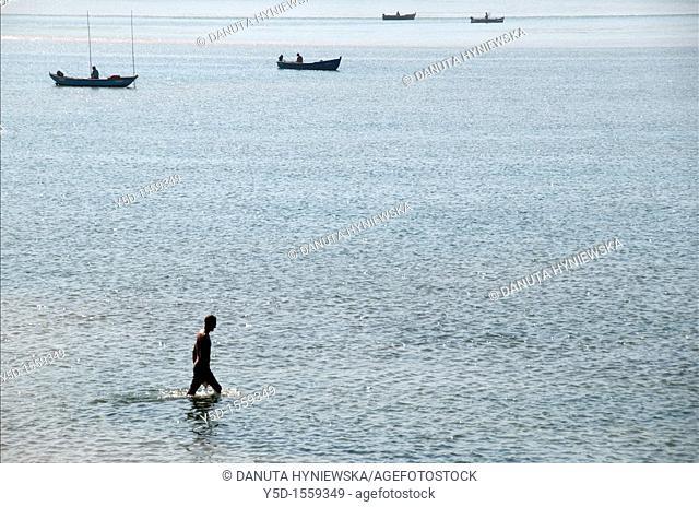 man walking in the water of Obidos Lagoon, Foz do Arelho, Slver Coast, Leiria district, Portugal, October