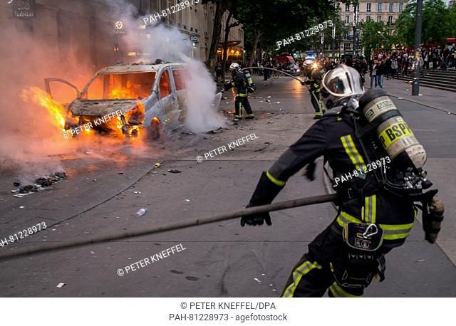 Firefighters put out a blaze from a burning car on the Place de la Republique in Paris, France, 14 June 2016. It came to riots on the margins of new protests...