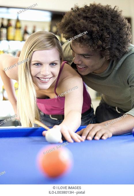 A teenage couple playing pool