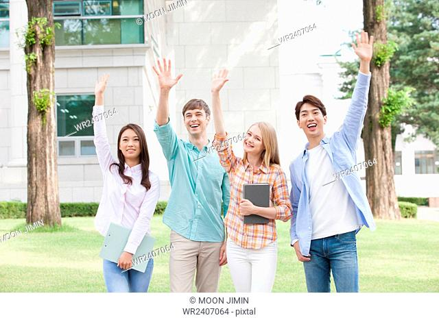 International students with domestic students in college waving their hands forward together and smiling outside on campus