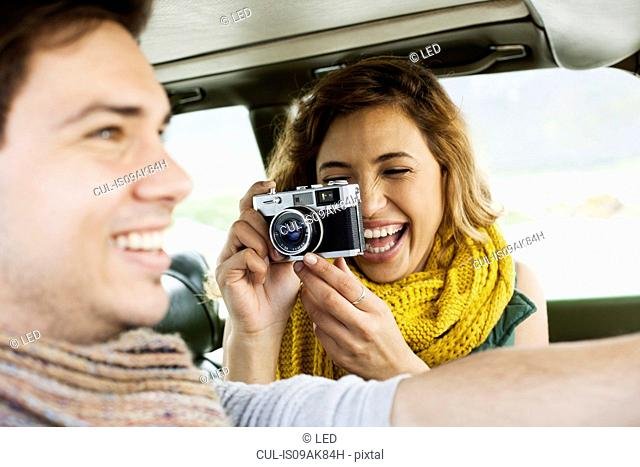 Young woman photographing boyfriend whilst driving, Cape Town, Western Cape, South Africa