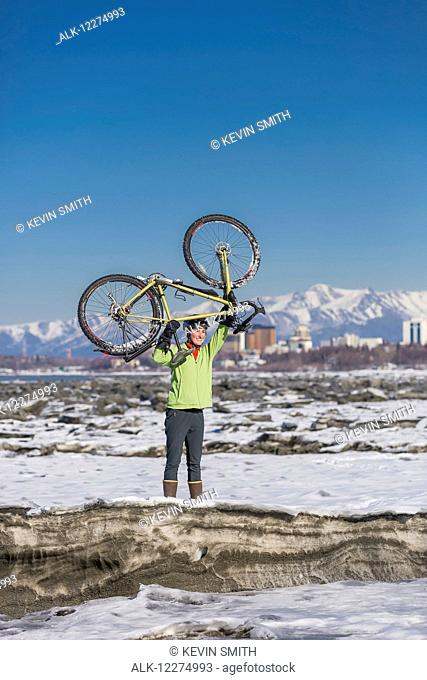 Young woman holding her bicycle over her head stands on frozen ice chunks along the Tony Knowles Coastal Trail, Anchorage, Southcentral Alaska