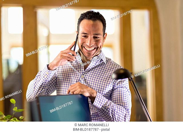 Hispanic businessman talking on cell phone in office