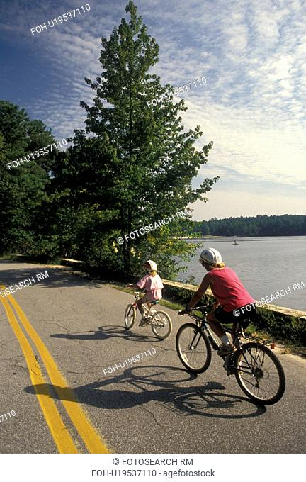 biking, mother, daughter, Stone Mountain, GA, Atlanta, Georgia, Mother and eight year old daughter biking with helmets on at Georgia's Stone Mountain Park in...