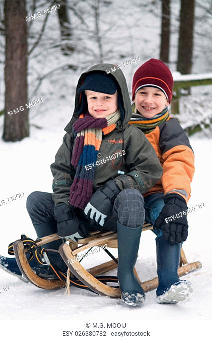Two young boys sitting on a sled in the snow