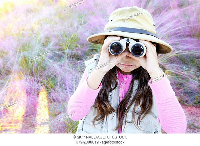 A young girl pretending to be on safari looking through binoculars