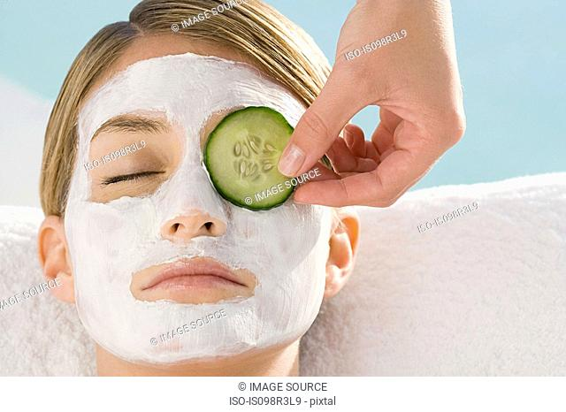 Young woman wearing facial mask having cucumber slice placed over eye