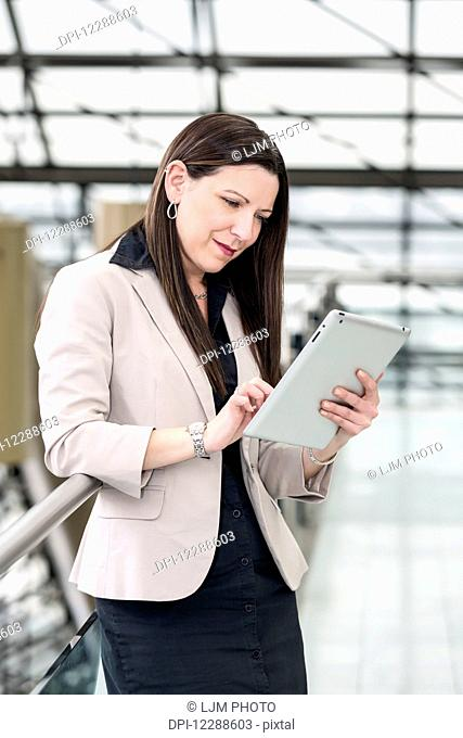 Mature business woman using her touch screen in an atrium; Edmonton, Alberta, Canada