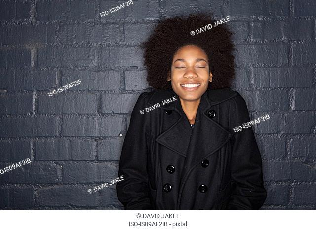 Young woman by black brick wall wearing black jacket