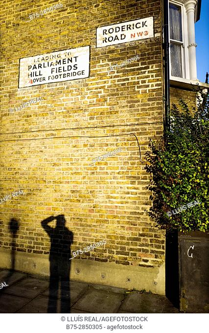 Facade of a single-family house with 'RODERICK ROAD NW3' 'Leading to PARLIAMENT HILL FIELDS Over Foot Bridge' signs and photographer's silhouette