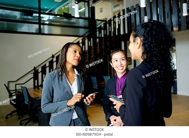 Three businesswomen standing in office, in conversation