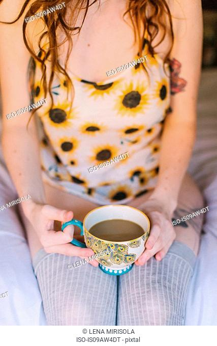 Young woman sitting on bed, holding teacup, mid section