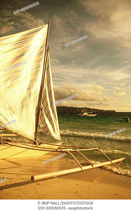 Catamaran sail blowing in the wind on shore of Boracay Island in the Plilippines