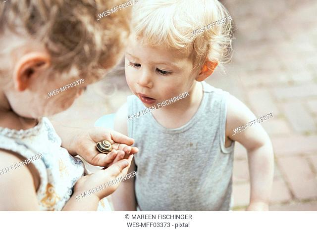 Little boy and girl looking at a snail in hand