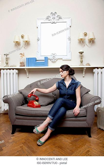 Woman on sofa picking up telephone handset