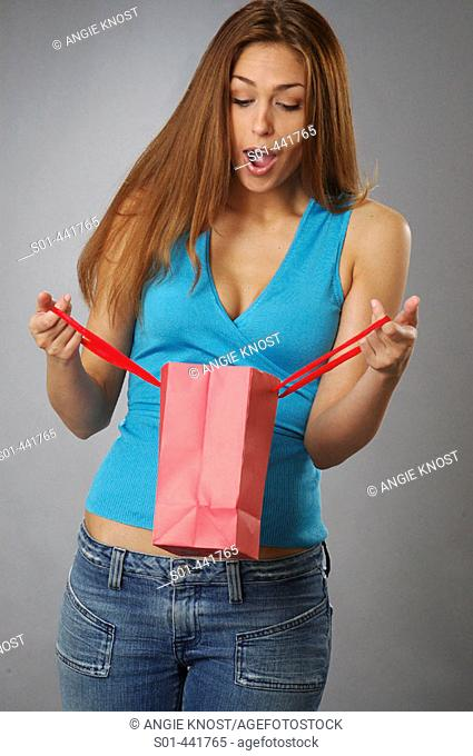 Young woman (20s) looking into gift bag with great surprise