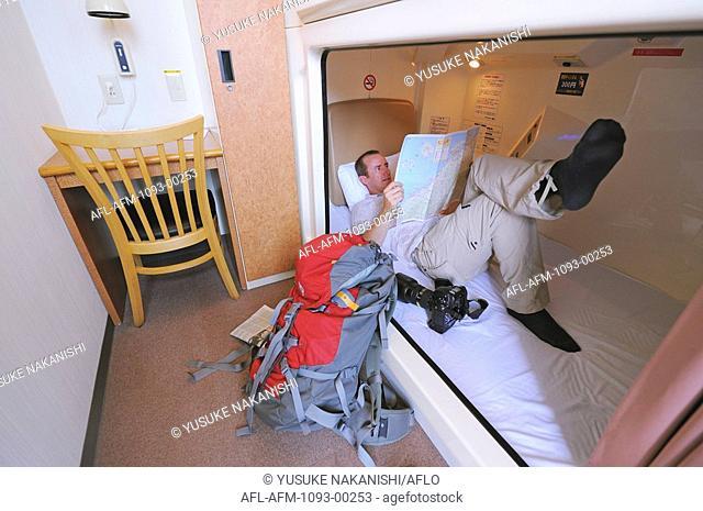 Man relaxing in pod of capsule hotel