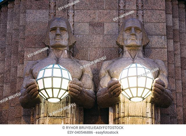 Helsinki, Finland. Night View Of Two Pairs Of Statues Holding The Spherical Lamps On Entrance To Helsinki Central Railway Station