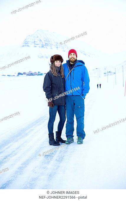Young couple standing on snow-covered road