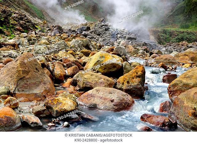 Small river winding down the hill through big rocks, coming from a hot spring of volcanic origin, with mineral rich water