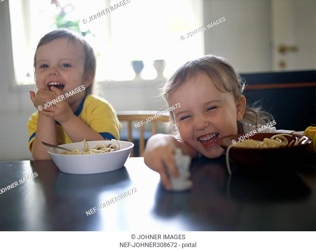 A boy and a girl eating pasta