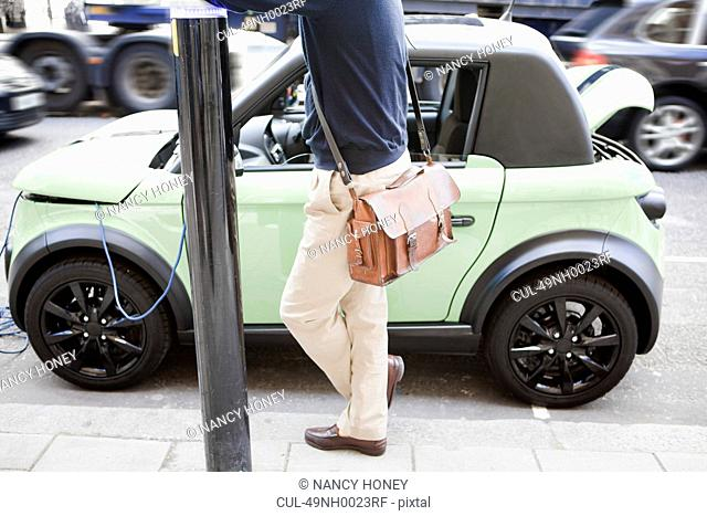 Man charging electric car on city street