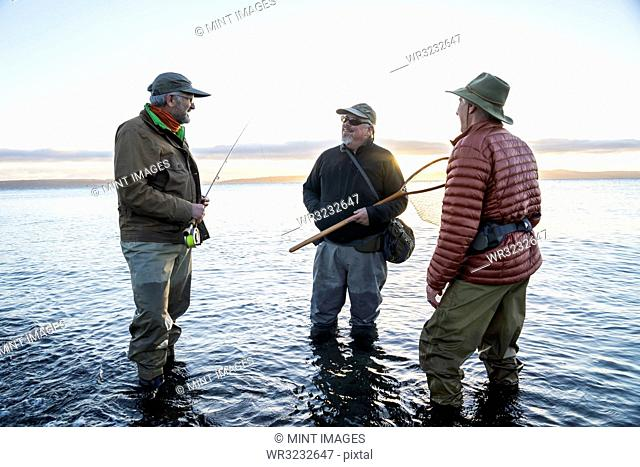 Two fly fisherman talk with their guide about new techniques while fly fishing for searun coastal cutthroat trout at a beach on the north west coastline of the...
